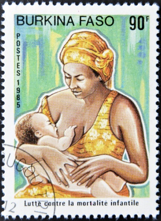 BURKINA FASO - CIRCA 1985: A stamp printed in Burkina Faso dedicated to combating child mortality, shows a mother breastfeeding her child, circa 1985 Stock Photo - 13289465