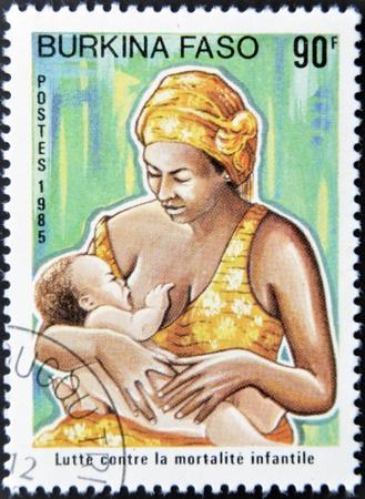 lactancia materna: BURKINA FASO - CIRCA 1985: Un sello impreso en Burkina Faso dedicada a la lucha contra la mortalidad infantil, muestra a una madre amamantando a su hijo, alrededor del a�o 1985 Editorial