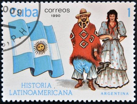 flag of argentina: CUBA - CIRCA 1990: Un sello impreso en Cuba dedicada a la historia de Am�rica Latina, muestra trajes t�picos y la bandera de la Argentina, alrededor de 1990