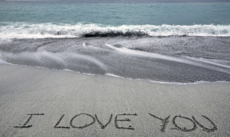 I love you written on the sand of a beach photo