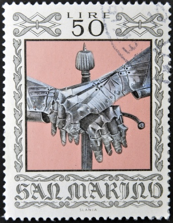 SAN MARINO - CIRCA 1974: A stamp printed in San Marino dedicated to Ancient Weapons from Cesta Museum, shows Gauntlets and Sword Pommel, circa 1974