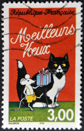 FRANCE - CIRCA 1997: A stamp printed in France shows mouse making him a gift to a cat, circa 1997 Stock Photo - 13749259