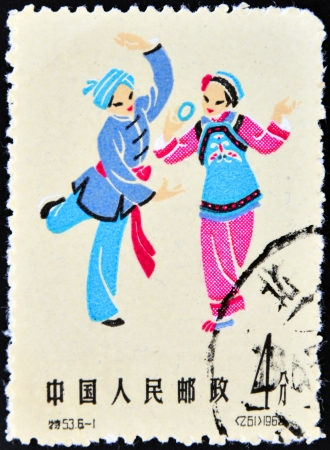 CHINA- CIRCA 1962. A stamp printed in China depicting traditional wear for women and men, circa 1962 photo