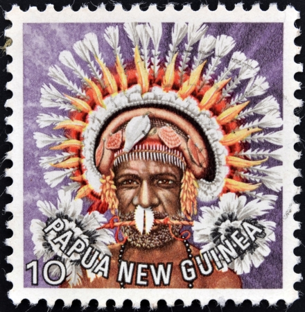 PAPUA NEW GUINEA - CIRCA 1977: stamp printed in  Papua New Guinea shows a man in a feathered headdress from the area near Koiari, circa 1977  photo