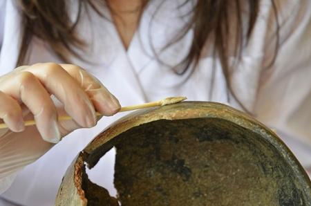restoring: woman restoring a prehistoric vessel