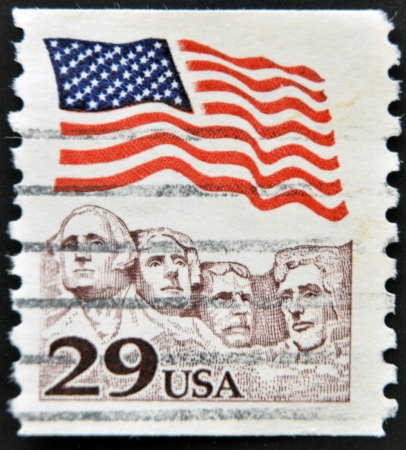'mt rushmore': UNITED STATES OF AMERICA - CIRCA 1991: A stamp printed in the USA shows American flag waving above Mt. Rushmore, circa 1991  Editorial
