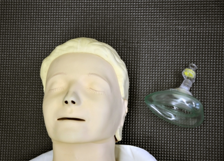 First aid medical practice dummy mannequin and assisted breathing mask photo