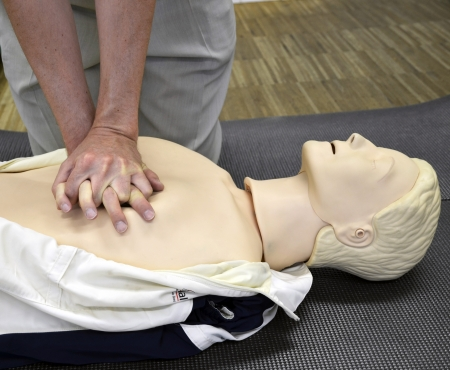 Man practicing CPR techniques on dummy.  photo