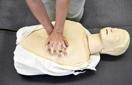cardiac: Man practicing CPR techniques on dummy.