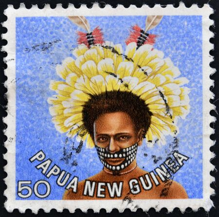 franked: PAPUA NEW GUINEA - CIRCA 1977  stamp printed in Papua New Guinea shows a man in a feathered headdress from the area near Koiari, circa 1977