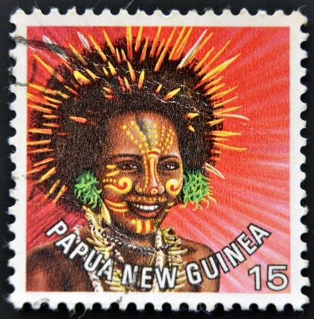 Nuova Guinea: PAPUA NUOVA GUINEA - CIRCA 1977 francobollo stampato in Papua Nuova Guinea, mostra una donna in un copricapo di piume dalla zona vicino Koiari, circa 1977 Archivio Fotografico