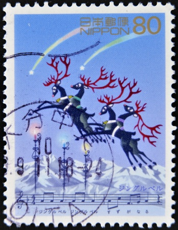 JAPAN - CIRCA 2000: A stamp printed in japan shows a Christmas scene with reindeer flying over the snow, circa 2000 photo