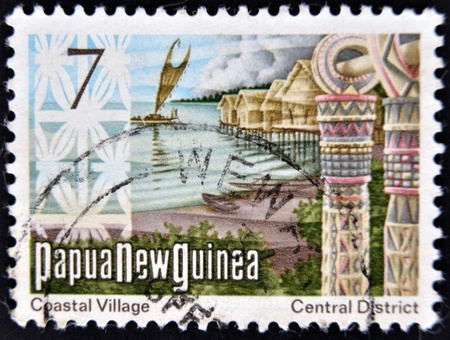PAPUA NEW GUINEA - CIRCA 1973  stamp printed in Papua New Guinea shows a coastal village with traditional houses on the sea, circa 1973  Stock Photo - 14434477