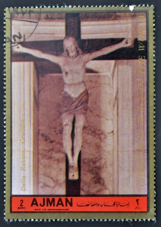 ajman: AJMAN - CIRCA 1972: A stamp printed in Ajman, Christmas collection, peace in the world, shows a sculpture of the crucifixion of Christ Della Robbia work , circa 1972