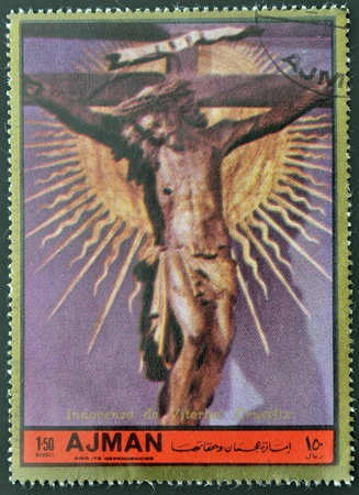 ajman: AJMAN - CIRCA 1972: A stamp printed in Ajman Christmas collection, peace in the world, shows a sculpture of the crucifixion of Christ work Inocenzo di Viterbo , circa 1972