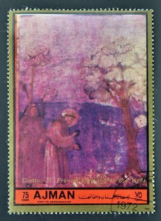 ajman: AJMAN - CIRCA 1972: A stamp printed in Ajman Christmas collection, peace in the world, shows a San Francisco fresco birds specking the work of Giotto, circa 1972