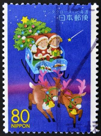 JAPAN - CIRCA 1999: A stamp printed in Japan,  shows children in a sleigh of Santa Claus, circa 1999  photo