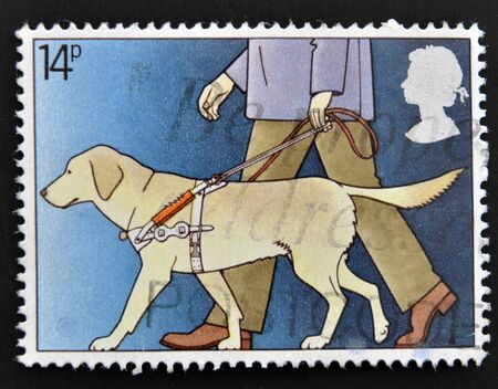 postal office: UNITED KINGDOM - CIRCA 1981: A stamp printed in Great Britain shows Blind Man with Guide Dog, circa 1981  Stock Photo