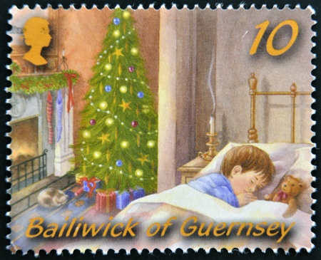 GUERNSEY - CIRCA 2005: A christmas stamp printed in Guernsey shows sleeping child on Christmas Eve, circa 2005 photo