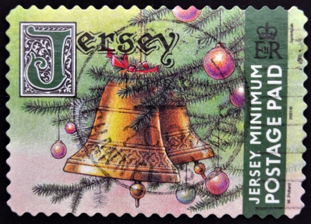 JERSEY - CIRCA 2002: A stamp printed in Jersey shows image of a bell and a Christmas tree, circa 2002  Stock Photo