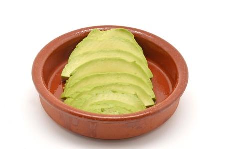 good cholesterol: avocado cut into clay bowl Stock Photo