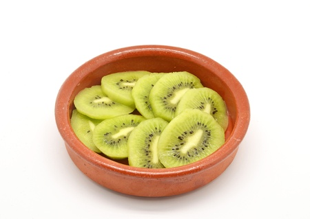 kiwi cut into clay bowl photo