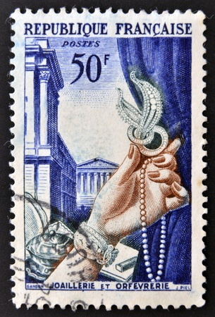 FRANCE - CIRCA 1938: A jewelry commemorative stamp printed in France shows wealthy woman's hand, circa 1938  Stock Photo - 15370502
