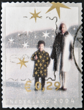 NETHERLANDS - CIRCA 2004: A christmas stamp printed in Holland shows woman and girl, circa 2004.