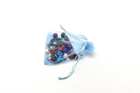 Blue cloth bag full of colored beads for jewelry photo