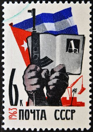 USSR - CIRCA 1963: A stamp printed in Russia shows Cuban flag, hands with gun and book, circa 1963