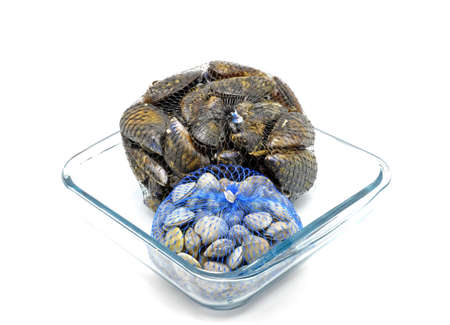 mussels and clams in two net bags on glass bowl photo