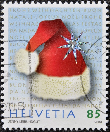helvetia: HELVETIA  SWITZERLAND  - CIRCA 2009  A christmas stamp printed in Switzerland shows christmas hat, circa 2009 Stock Photo