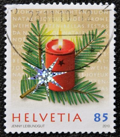 helvetia: HELVETIA  SWITZERLAND  - CIRCA 2009  A christmas stamp printed in Switzerland shows candle Stock Photo