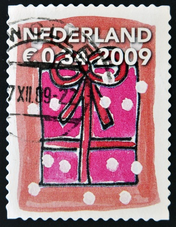 HOLLAND - CIRCA 2009: A stamp printed in Holland shows gift box with ribbon, circa 2009 Stock Photo - 16136415