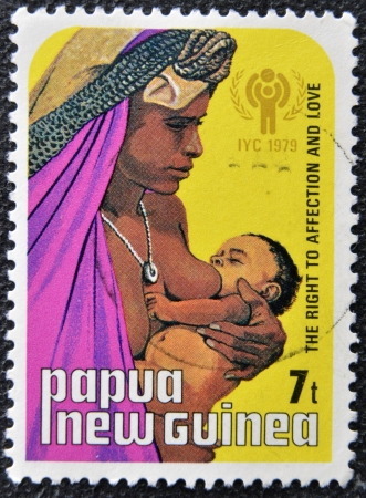 PAPUA NEW GUINEA - CIRCA 1979  A stamp printed in Papua shows a mother breastfeeding her child, circa 1979 Stock Photo - 16127736