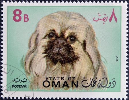 OMAN - CIRCA 1971: stamp printed in Oman, shows a Pekingese dog breed, circa 1971 photo