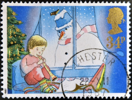 UNITED KINGDOM - CIRCA 1987: A stamp printed in Great Britain dedicated to Christmas, shows Child playing Flute and Snowman, circa 1987 Stock Photo - 16306927