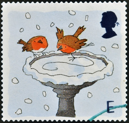 UNITED KINGDOM - CIRCA 2001: A stamp printed in England, is dedicated to Christmas, shows Robins skating on Bird Bath, circa 2001  photo
