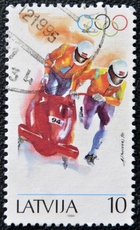 to steer a sledge: LATVIA - CIRCA 1994: A stamp printed in Latvia dedicated to Two-man bobsled, circa 1994
