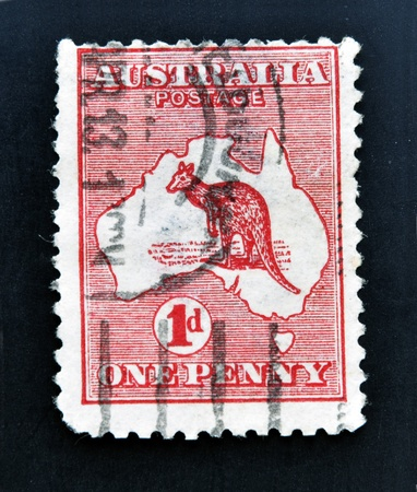 AUSTRALIA - CIRCA 1913: stamp printed in Australia shows kangaroo in the map, one penny, circa 1913  photo