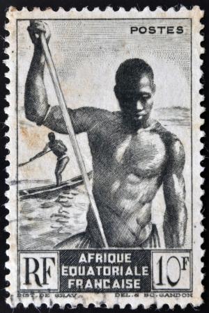 FRENCH EQUATORIAL AFRICA - CIRCA 1947: A stamp printed in former French Equatorial region of Africa shows men canoe, circa 1947