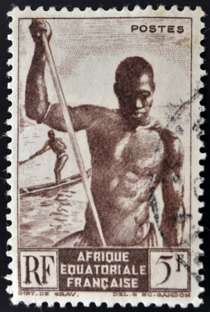 FRENCH EQUATORIAL AFRICA - CIRCA 1947: A stamp printed in former French Equatorial region of Africa shows men canoe, circa 1947  photo