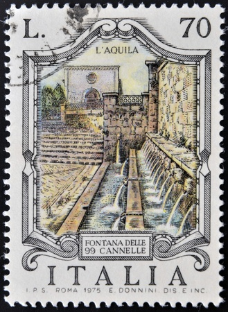 ITALY - CIRCA 1975: stamp printed in Italy shows Fountain of the 99 faucets in Aquila, circa 1975