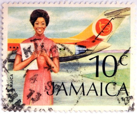 jamaican ethnicity: JAMAICA - CIRCA 1972: Stamp printed in Jamaica shows A Flight Attendant Standing In Front Of An Air Jamaica Airplane, circa 1972