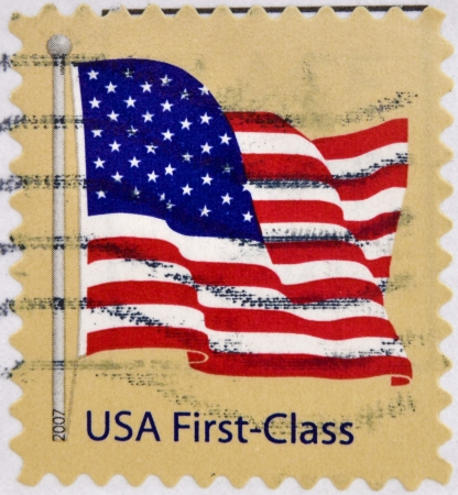 UNITED STATES OF AMERICA - CIRCA 2007  A stamp printed in USA shows waving USA flag, first-class, circa 2007  photo