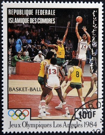 comores: COMORES - CIRCA 1984: A stamp printed in Comores dedicated to the Olympic Games in Los Angeles 1984, shows basketball, circa 1984