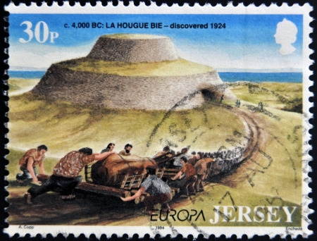 discovered: JERSEY - CIRCA 1994: Stamp printed in Jersey shows La Hougue Bie, discovered 1924, circa 1994 Stock Photo