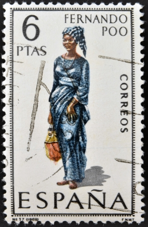 SPAIN - CIRCA 1968: A stamp printed in Spain dedicated to Provincial Costumes shows a woman from Fernando Poo, circa 1968 photo