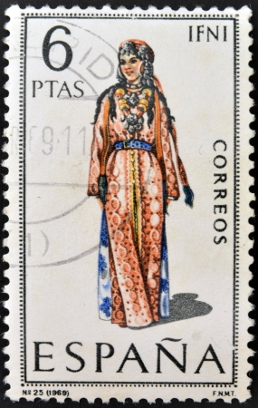 SPAIN - CIRCA 1969: A stamp printed in Spain dedicated to Provincial Costumes shows a woman from Ifni, circa 1969 Stock Photo - 20009917