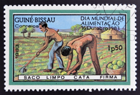 GUINEA BISSAU - CIRCA 1983: a stamp printed in the Republic of Guinea-Bissau commemorative the world food day, showing farmers plowing the land, circa 1983.  Stock Photo - 20398581